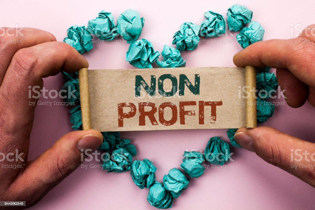 Word writing text Non Profit. Business concept for Charitable Wrothless Philanthropy Aid Unlucrative Profitless written on Cardboard Paper Holding by man plain background on Heart Paper Balls. stock photo