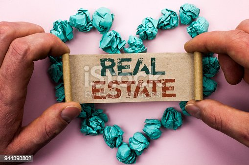 istock Word writing text Real Estate. Business concept for Residential Property Building Covered Land Chattels Real written on Cardboard Paper Holding by man plain background on Heart Paper Balls. 944393802
