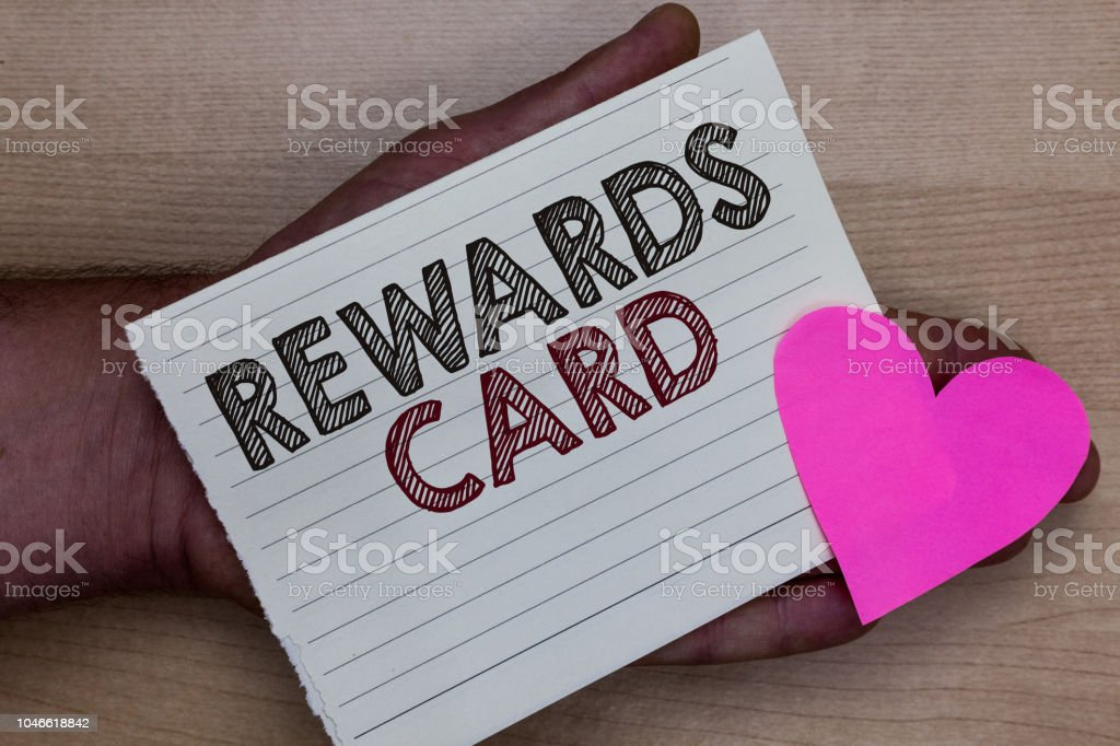 Word writing text Rewards Card. Business concept for Help earn cash points miles from everyday purchase Incentives Man holding piece notebook paper heart Romantic ideas messages feelings. stock photo