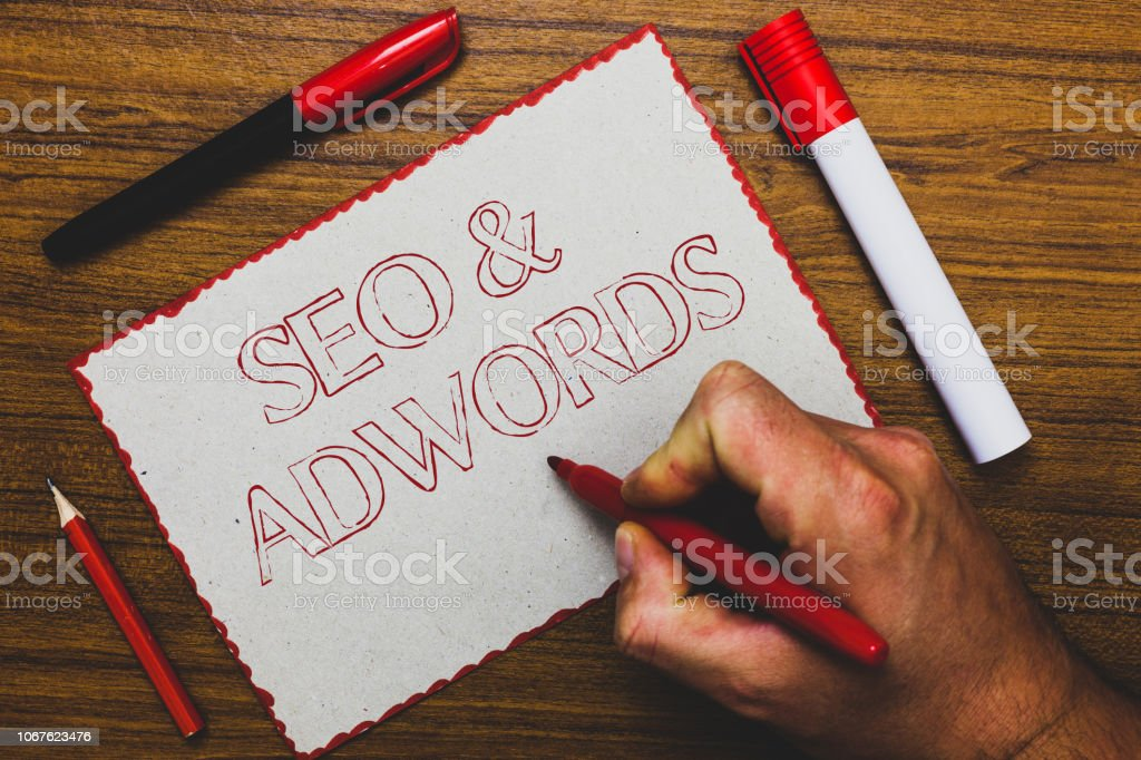 Word writing text Seo and Adwords. Business concept for Pay per click Digital marketing Google Adsense Man hand holding marker notebook paper expressing ideas wooden background. – zdjęcie