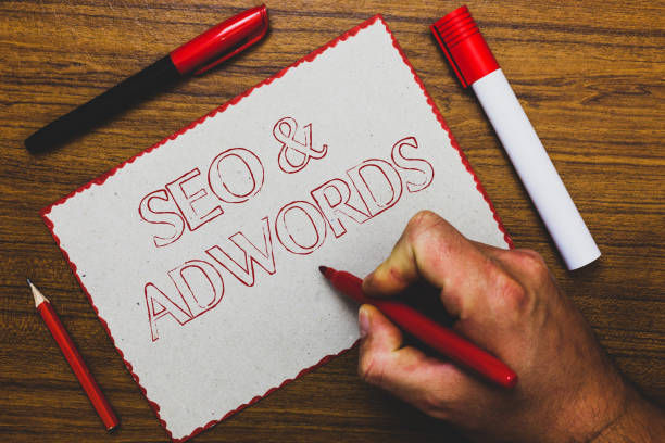 Word writing text Seo and Adwords. Business concept for Pay per click Digital marketing Google Adsense Man hand holding marker notebook paper expressing ideas wooden background. stock photo