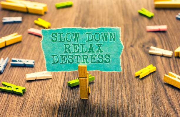 Word writing text Slow Down Relax Destress. Business concept for calming bring happiness and put you in good mood Clothespin holding turquoise paper note several clothespins wooden floor. stock photo