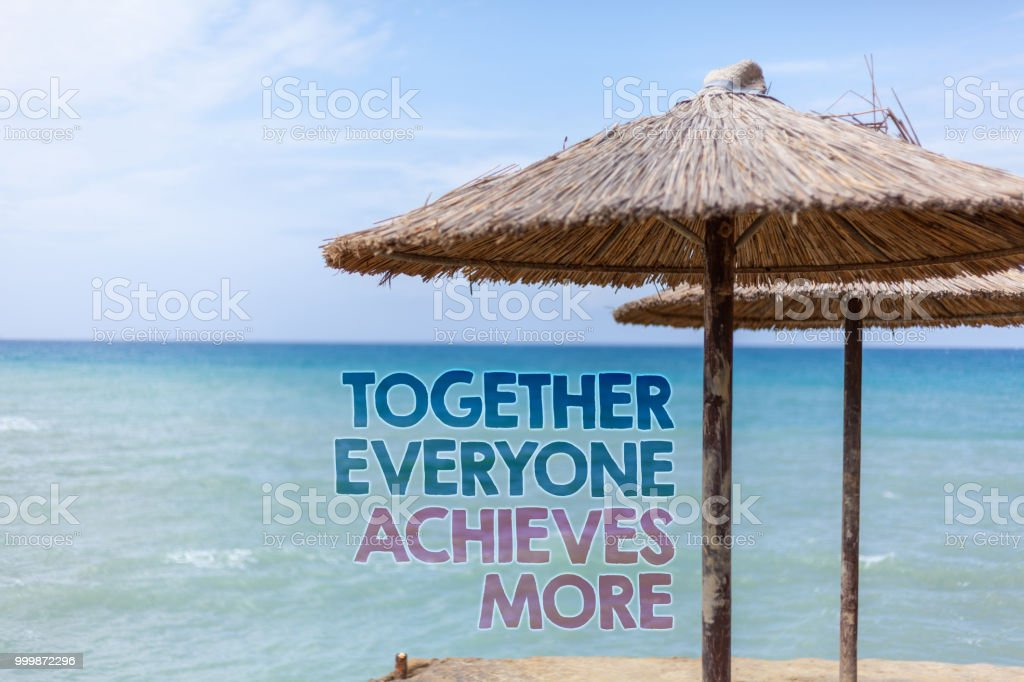 Word writing text Together Everyone Achieves More. Business concept for Teamwork Cooperation Attain Acquire Success Blue beach water Thatched Straw Umbrellas Message Ideas Thoughts Reflection. stock photo