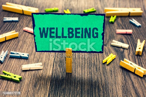 istock Word writing text Wellbeing. Business concept for A good or satisfactory condition of existence including health Clothespin holding green paper note several clothespins wooden floor. 1046617278