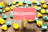 istock Word writing text Willkommen. Business concept for welcoming people event or your home something to that effect Clothespin holding pink note paper crumpled papers several tries mistakes. 1046619320