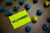 istock Word writing text Willkommen. Business concept for welcoming people event or your home something to that effect Yellow piece paper reminder lots crumpled papers several tries wooden floor. 1046619364