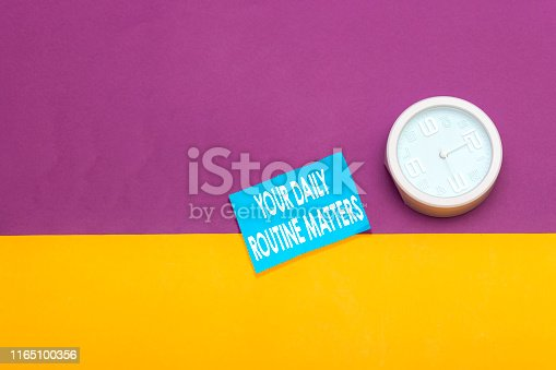 Word writing text Your Daily Routine Matters. Business concept for practice of regularly doing things in fixed order Metal alarm clock wakeup blue notepad colored background.