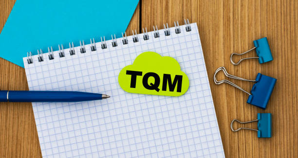 tqm - word written in a notebook on a wooden background with a pen and clamps - depositor stock pictures, royalty-free photos & images