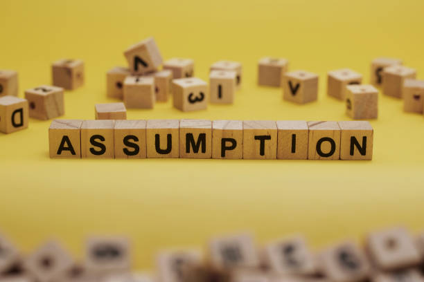 ASSUMPTION Word Written In Wooden Cube With Yellow Background stock photo