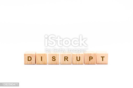 DISRUPT word written in wooden cubes on a white background with copy space