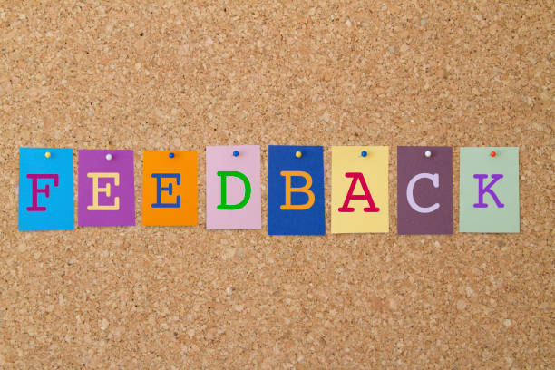 FEEDBACK word written on colorful sticky notes pinned on cork board. stock photo
