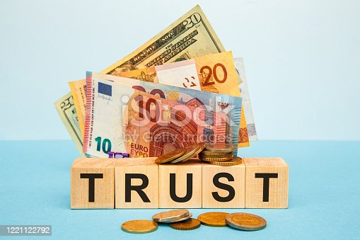 939533958 istock photo TRUST word written on wood cubes on the background of various banknotes. 1221122792