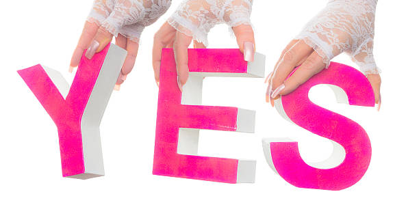 Word yes hold up by bridal hands stock photo