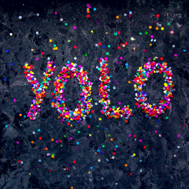 Word 'YOLO' made of colorful confetti on black textured background. stock photo