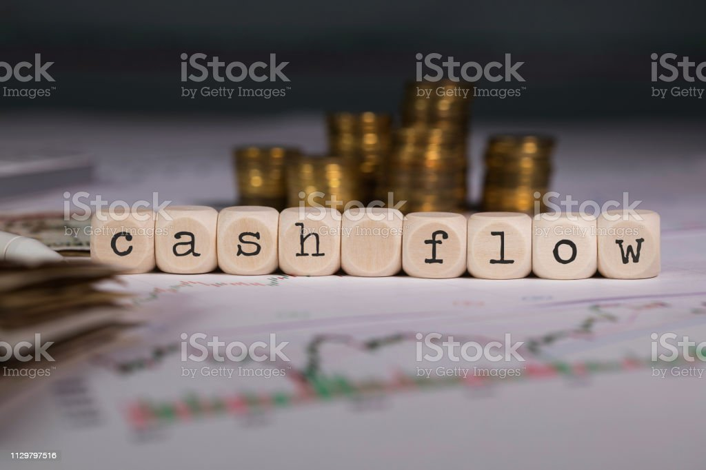 Words CASH FLOW composed of wooden letters. Words CASH FLOW composed of wooden letters. Stacks of coins in the background. Closeup Business Stock Photo