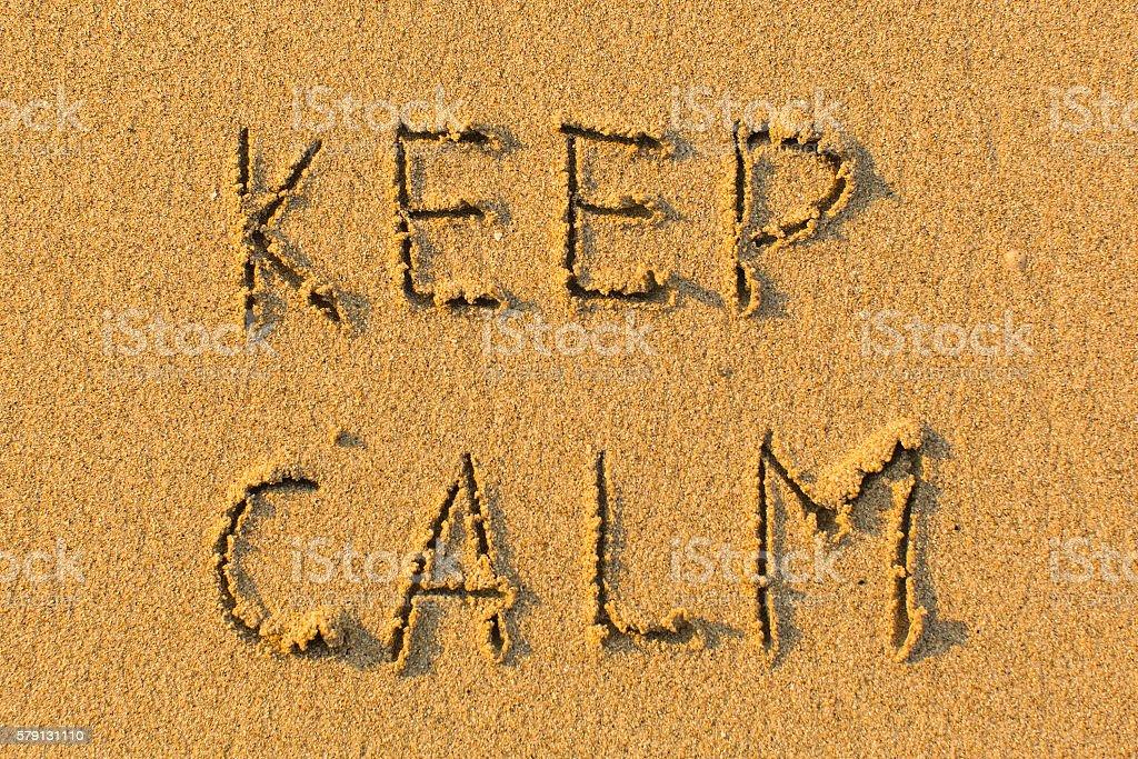 KEEP CALM - words hand-written on sand beach. stock photo