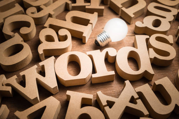 Words Have Power Words alphabets in scettered wood letters on the table with glowing light bulb as communication idea or words have power concept single word stock pictures, royalty-free photos & images