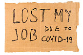 words lost my job due to covid-19 handwritten on rectangular flat sheet of cardboard - homeless placard, isolated on white background