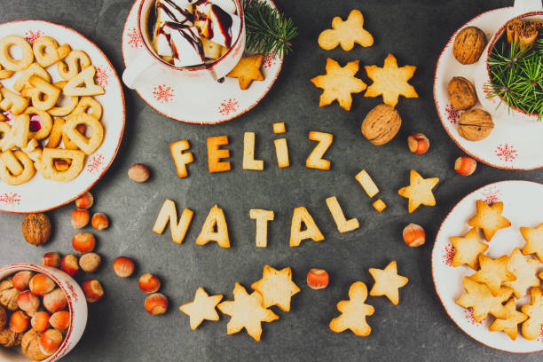 FELIZ NATAL COOKIES. Words Merry Christmas en portuguese with baked cookies, Christmas decoration and nuts on black slate background. Christmas card for portuguese speaking countries top view. stock photo