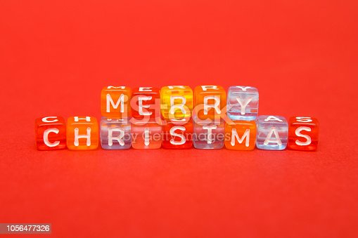 istock words merry christmas made of colorful blocks on red background. Flat lay, top view - holidays, winter, christmas and new year celebration concept. 1056477326