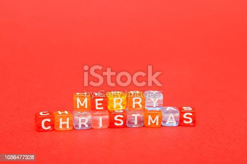 istock words merry christmas made of colorful blocks on red background. Flat lay, top view - holidays, winter, christmas and new year celebration concept. copyspace. 1056477328