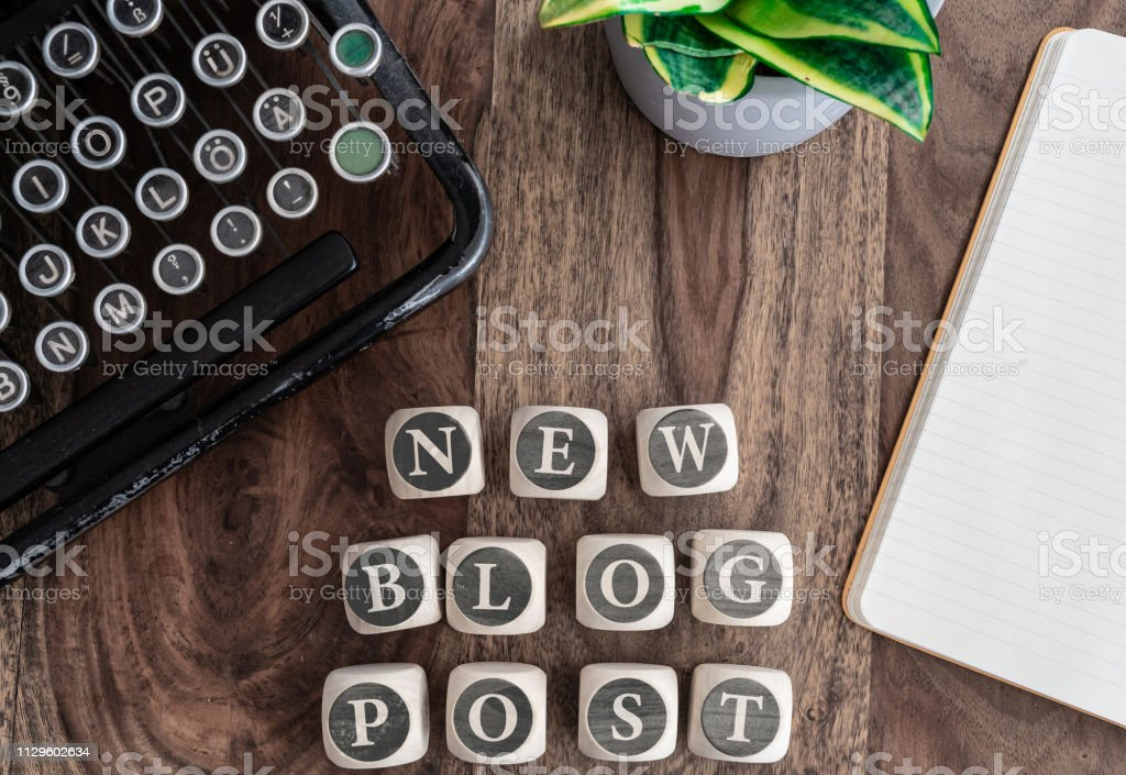words NEW BLOG POST on wooden blocks on table with note pad, potted plant and vintage typewriter top view of words NEW BLOG POST on wooden blocks on table with note pad, potted plant and vintage typewriter Article Stock Photo