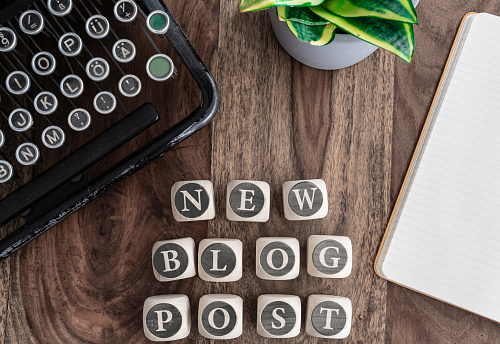 Words New Blog Post On Wooden Blocks On Table With Note Pad Potted Plant And Vintage Typewriter Stock Photo - Download Image Now