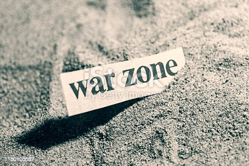 Newspaper headline - war zone - in sand.