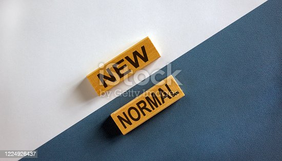 NEW NORMAL words on wooden blocks. New normal concept. Beautiful wooden background.
