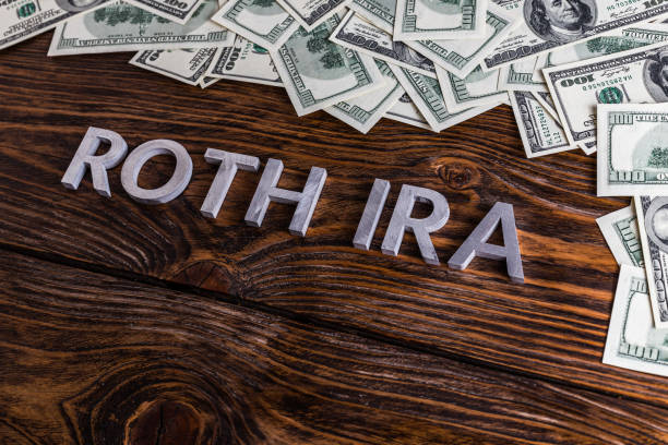words ROTH IRA laid on wooden surface with metal letters and us dollar banknotes stock photo
