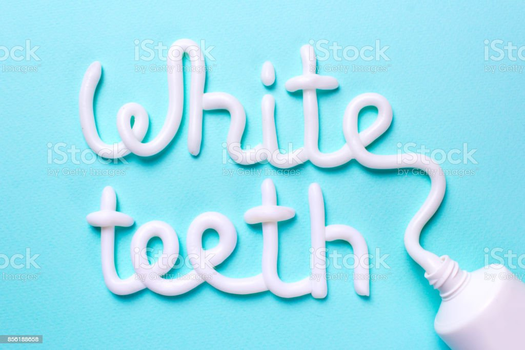 Words white teeth from toothpaste. Tube and toothbrush for cleaning teeth and whitening stock photo