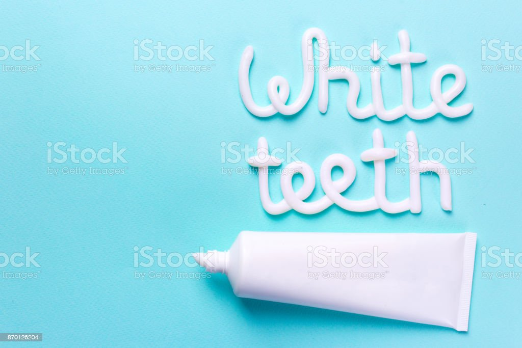 Words white teeth from toothpaste. Tube and toothbrush for cleaning teeth and whitening. Copy space for text stock photo