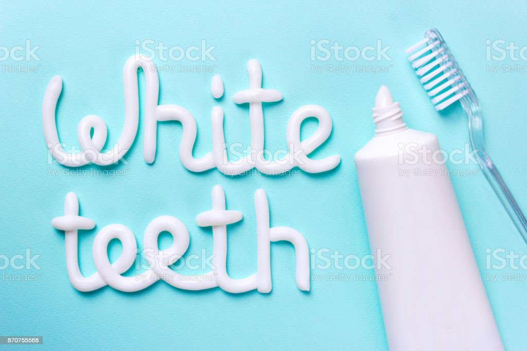 Words white teeth from toothpaste. Tube for cleaning teeth and whitening stock photo