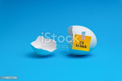 istock I WILL BE BACK words written on broken eggs shell over blue background. 1143227134