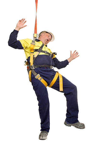 Work Accident Man fitted with safety harness falling from height. safety harness stock pictures, royalty-free photos & images