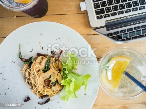 Work and eat, Spaghetti spicy stir fried taste and grilled chicken and lemonade and computer , top view on wooden table.