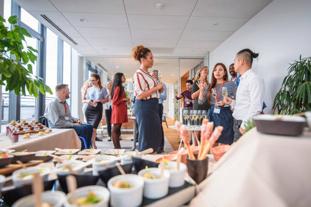 Work Associates Enjoying Food and Sparkling Wine at Party Low angle view of gourmet small dishes in foreground and corporate professionals networking at new business launch party. publicity event stock pictures, royalty-free photos & images