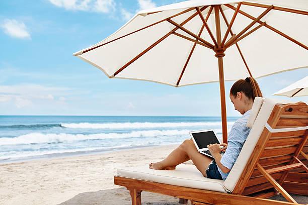 work at beach. business woman working online on laptop outdoors - sonnenschirm terrasse stock-fotos und bilder