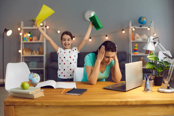 Work at home is stressful. Tired mother with stress working with a laptop at home. stock photo