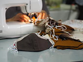 Work at home woman sitting sewing a fabric mask, for dust and germs pm 2.5, virus covid 19