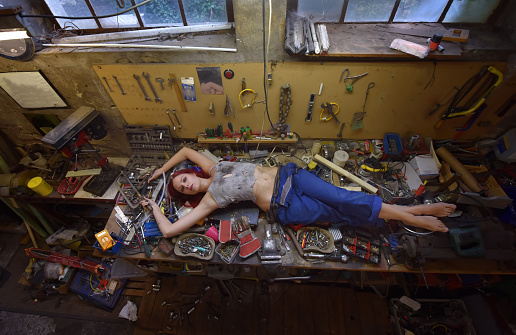 A young beautiful woman finds time to relax during  her working hours. She lies down on the work bench filled with tools and other electronic devices.