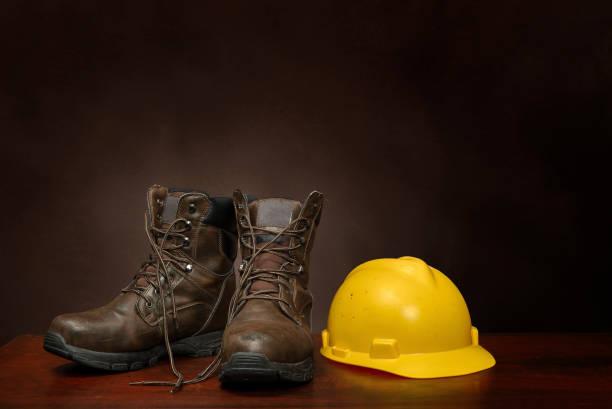 Arbeitsstiefel und Bauhelm auf der Braune mit Kopierplatz – Foto