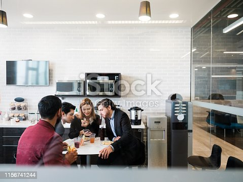 A group of work colleagues sitting around a table looking at a cellphone during their coffee break.