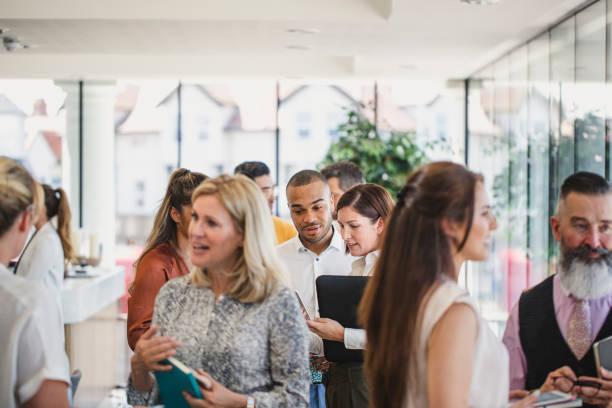 colleghi di lavoro che si incontrano e parlano nell'edificio aziendale - evento foto e immagini stock