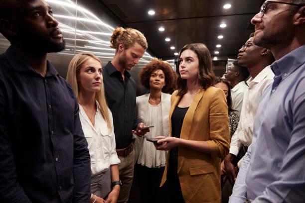 los compañeros de trabajo están esperando juntos en un ascensor en su oficina - lleno fotografías e imágenes de stock