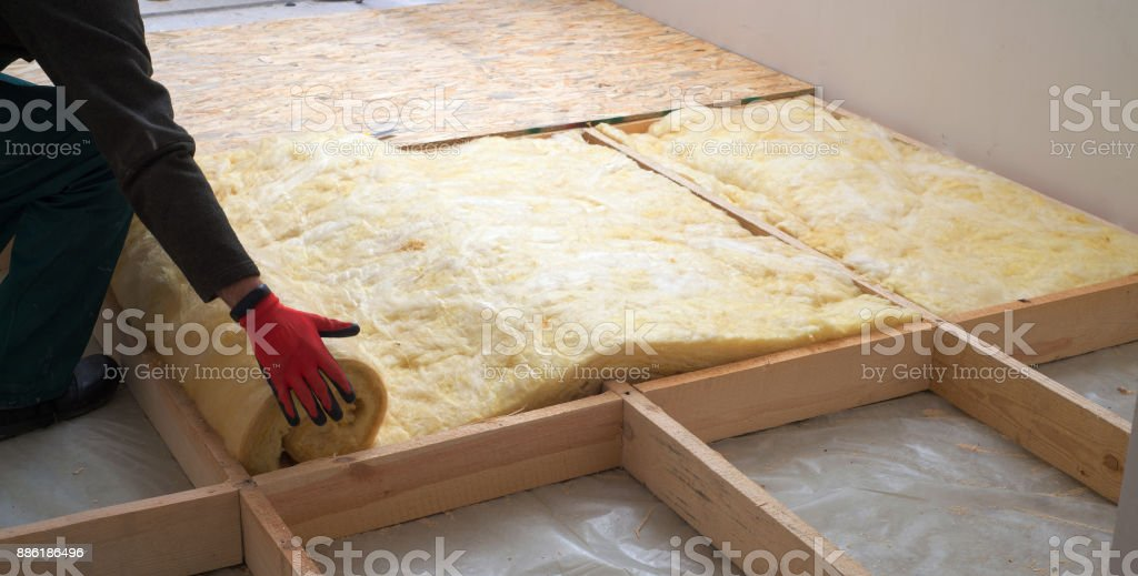 Work composed of mineral wool insulation in the floor, floor heating insulation , warm house, eco-friendly insulation, a builder at work stock photo