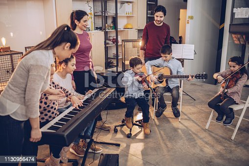 Group of people, teachers and children in music school, learning to play music instruments together.