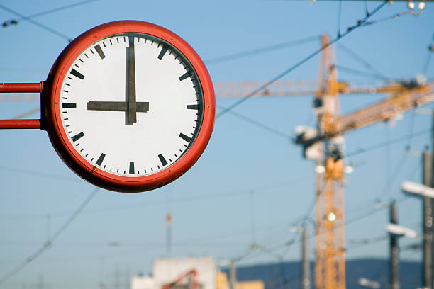 Work Day The clock strikes 9AM as the work day begins near a construction site. Photo has shallow DOF, with main focus on the clock. davelongmedia stock pictures, royalty-free photos & images