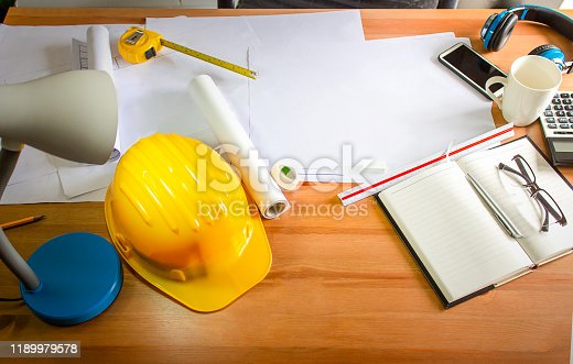 898133862 istock photo Work desk and architect's work equipment in the office, Yellow safety hard hat 1189979578