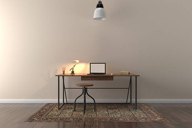 Work desk in empty room with big wall in background stock photo